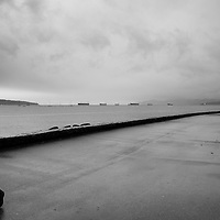 Sillhouetted man with an umbrella in the rain, walking out of the frame. Stormy skies on the horizon.