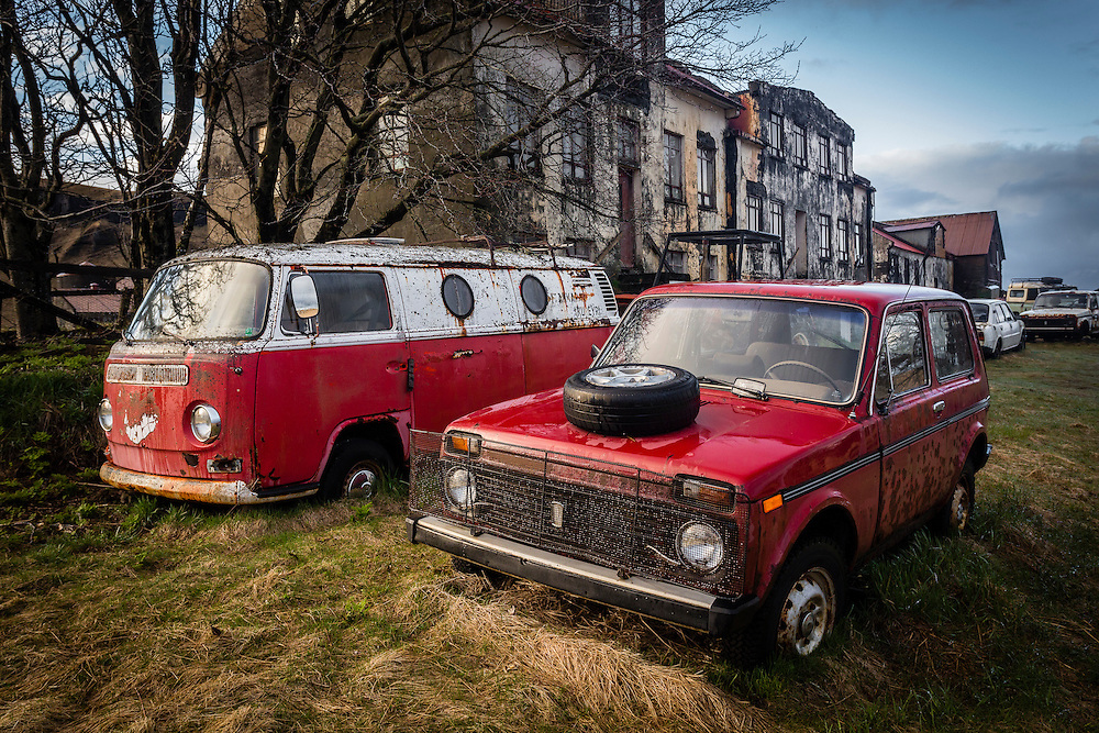 A VW camper van and a Lada Niva stand side by side, abandoned at Holmur