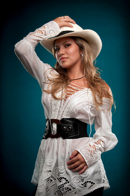 Sensual woman cowgirl posing with hat and smiling.