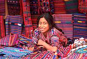 GUATEMALA, MARKETS Sololá; Mayan girl selling textiles