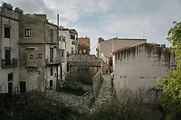 "SUTERA, ITALY - 8 JANUARY 2018: A woman hangs clothes on her balcony in the historical center of Sutera, Italy, on January 8th 2018.<br /> <br /> Sutera is an ancient town plastered onto the side of an enormous monolithic rock, topped with a convent, in the middle of the western half of Sicily, about 90 minutes by car south of the Sicilian capital Palermo<br /> Its population fell from 5,000 in 1970 to 1,500 today. In the past 3 years its population has surged  after the local mayor agreed to take in some of the thousands of migrants that have made the dangerous journey from Africa to the Sicily.<br /> <br /> ""Sutera was disappearing,"" says mayor Giuseppe Grizzanti. ""Italians, bound for Germany or England, packed up and left their homes empty. The deaths of inhabitants greatly outnumbered births. Now, thanks to the refugees, we have a chance to revive the city.""<br />  Through an Italian state-funded project called SPRAR (Protection System for Refugees and Asylum Seekers), which in turn is co-funded by the European Union's Fund for the Integration of non-EU Immigrants, Sutera was given financial and resettlement assistance that was co-ordinated by a local non-profit organization called Girasoli (Sunflowers). Girasoli organizes everything from housing and medical care to Italian lessons and psychological counselling for the new settlers.<br /> The school appears to have been the biggest beneficiary of the refugees' arrival, which was kept open thanks to the migrants.<br /> Nunzio Vittarello, the coordinator of the E.U. project working for the NGO ""I Girasoli"" says that there are 50 families in Sutera at the moment."