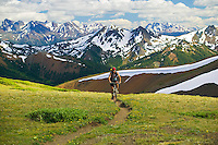 A mountain bike rider riding to the summit of Windy Pass is dwarfed by the breathtaking Southern Chilcotin Mountains behind him.  Gold Bridge, Southern Chilcotin Mountains, British Columbia, Canada.