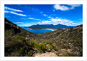 Wide-angle view of Wineglass Bay and surrounding granite mountains [Freycinet NP, Tasmania, Australia]<br /> <br /> Image ID: 201679. Order by email to orders@girtbyseaphotography.com quoting the image ID, preferred print size &amp; media. Current standard size prices are published on the Pricing page. Custom sizes also available.