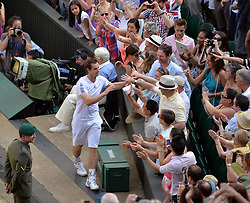 © London News Pictures. 07/07/2013 . London, UK. Andy Murray celebrates with the crowd after his men's singles final victory over Novak Djokovic of Serbia at the Wimbledon Lawn Tennis Championships final, becoming the first British male to win the tournament in 77 years. Photo credit: Mike King/LNP