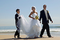 Bride and Groom with brother walking on beach