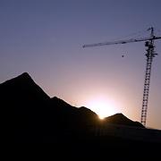Oman, Ar Rustaq. January/29/2008...A building crane looms as the sun sets over the Western Hajars.