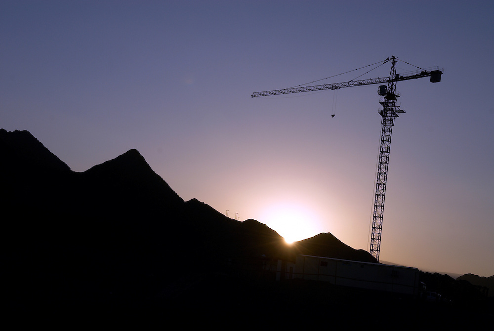 Oman, Ar Rustaq. January/29/2008...A building crane looms as the sun sets over the Western Hajars.