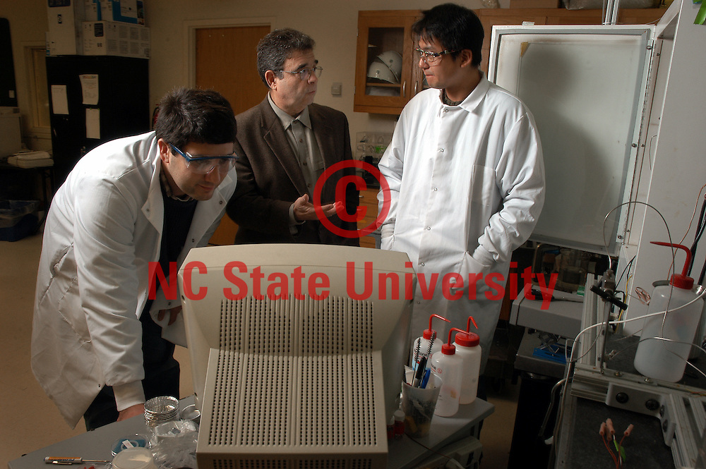 Dr. Ruben Carbonell (center) checks in on chemical engineering students as they work on a Kenan Center for the Utilization of Carbon Dioxide in Manufacturing project in a Partners II lab on Centennial Campus.   photo by Roger Winstead