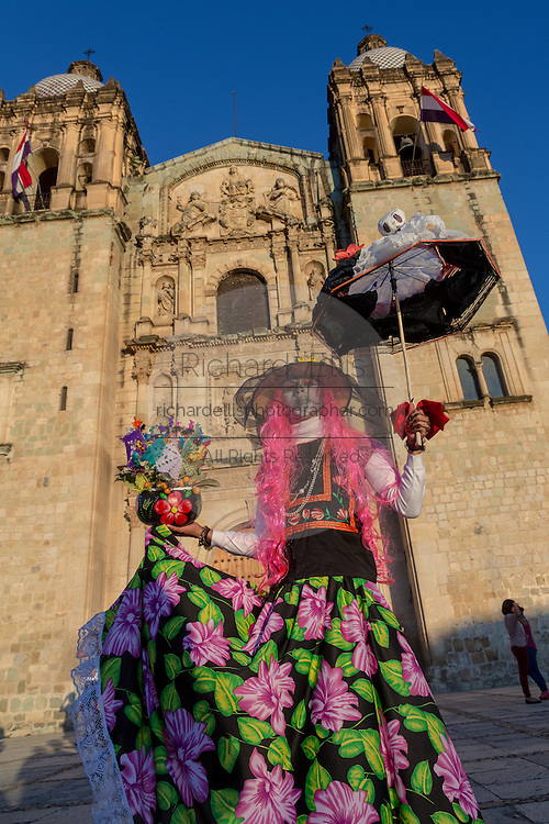 A young man dressed as a skeleton bride poses in front of the Santo Domingo church during the Day of the Dead Festival known in spanish as Día de Muertos on October 25, 2014 in Oaxaca, Mexico.