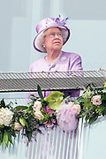 © Licensed to London News Pictures. 07/06/2014. Epsom, UK. HRH Queen Elizabeth II watches the Derby from the balcony of the grandstand. . Derby Day today 7th June 2014 at Epsom 2014 Investic Derby Festival in Surrey. Traditionally, elegant, fashionable racegoers gather for a classic day's racing at Epsom Racecourse, Surrey. Photo credit : Stephen Simpson/LNP