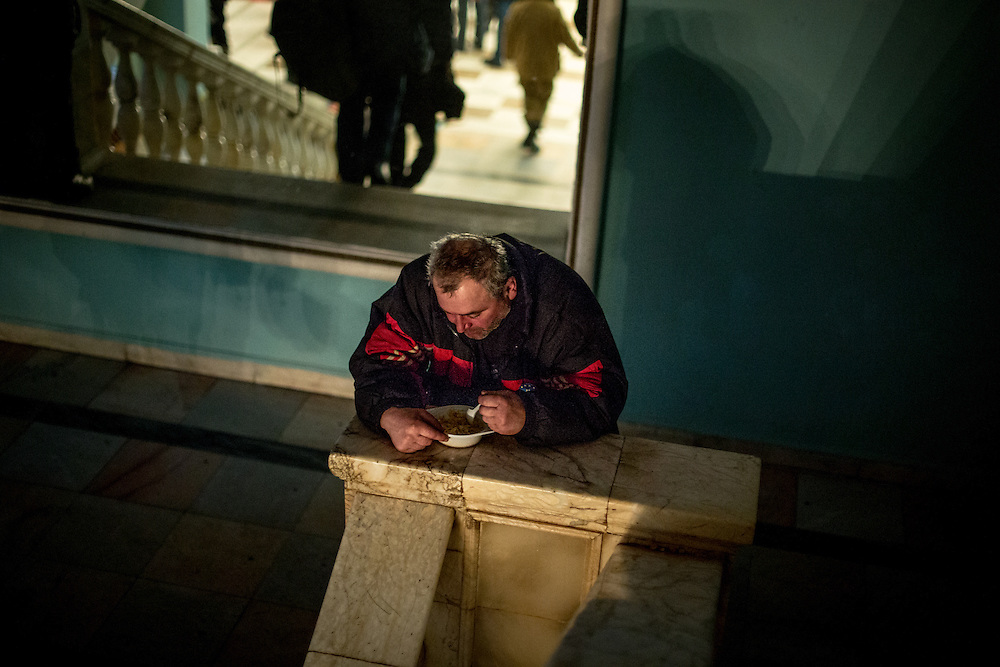 A man eats in the stairs of the Center of Ukrainian Culture, occupied by the protesters.