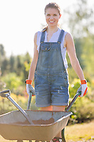 Portrait of happy female gardener pushing wheelbarrow at garden