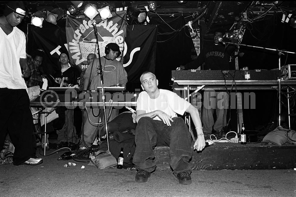 NEW YORK - MARCH 1999:  Rapper Eminem, seated, and unidentified rappers and DJs on turntables in background, perform at Tramps in March 1999 in New York City, New York. (Photo by Catherine McGann)Copyright 2010 Catherine McGann