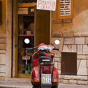 Vespa scooter parked outside alimentari and sandwich shop in Deruta, Italy<br />