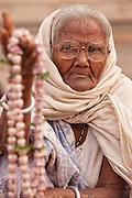 Am elderly woman sells prayer beads on the street near the Mani Karnika (Main) Ghat in the Old City of Varanasi India