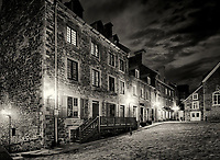 Illuminated corner of the Royal Square in Old Quebec City with its beautiful historic architecture and dramatic night sky. Black and white. Quebec, Canada. Place Royale, Ville de Québec.