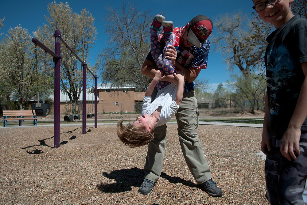 "mkb032417/metro/Marla Brose --  Joe Garcia holds his niece Riley Clark, 5, upside down while playing with his children, niece and nephew at Los Duranes Park in Albuquerque, N.M., Friday, March 24, 2017. Garcia spent several days with the children during this week's Spring Break. All the children go back to school Monday. ""I like doing fun things with my kids,"" Garcia said. (Marla Brose/Albuquerque Journal)"