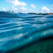 Split shot of ocean surface and blue sky, Cozumel, Mexico.