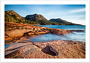Late afternoon sun lights up the granite rocks at Honeymoon Bay, with The Hazards in the background [Freycinet NP, Tasmania]<br />