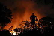 San Marcos, California, U.S. - <br /> <br /> California Wildfires 2014 - Cocos Fire<br /> <br /> A homeowner looks from a rock as a fire approaches his home as firefighters battle the Cocos fire near Cal State San Marcos on Wednesday, May 14, 2014 in San Diego County, Calif. The fire in San Marcos burned out of control Wednesday, destroying houses and forcing nearby residents from their homes. The fire burned at least three homes and one structure near Cal State San Marcos.<br /> ©Exclusivepix