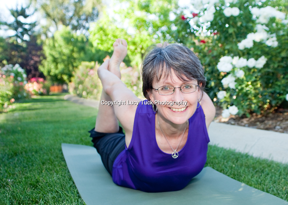 Natural picture of a yoga instructor demonstrating boat pose in a rose garden.