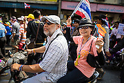 05 JANUARY 2014 - BANGKOK, THAILAND: A couple on a motorcycle rides through an anti-government march in Bangkok. Suthep Thaugsuband, leader of the anti-government protests in Bangkok, led the protestors on a march through the Chinatown district of Bangkok. Tens of thousands of people waving Thai flags and blowing whistles gridlocked what was already one of the most congested parts of the city. The march was intended to be a warm up to their plan by protestors to completely shut down Bangkok starting Jan. 13.     PHOTO BY JACK KURTZ
