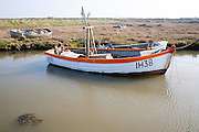 Small fishing boats moored in tidal inlet on the River Alde at Slaughden, Aldeburgh, Suffolk, England