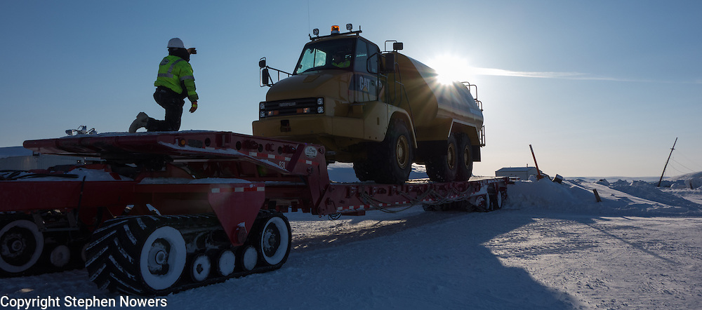 A spotter helps unload a Cruz Construction water truck in Umiat, Alaska after a 100-mile trek across the tundra from the Dalton Highway. Cruz Construction is supporting Linc Energy's exploratory drilling effort in the National Petroleum Reserve Alaska during the 2012-13 drilling season.