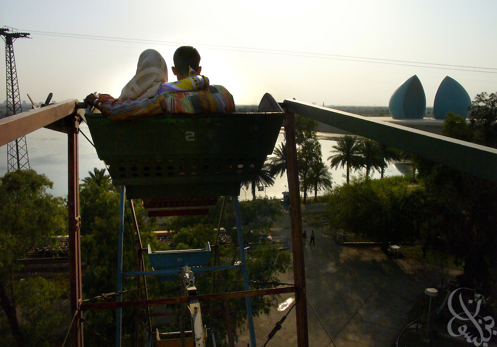 An Iraqi couple ride a ferris wheel May 27, 2006 in the Fun Land amusement park in eastern Baghdad.