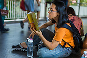 "31 MAY 2014 - BANGKOK, THAILAND: People walk by a man sitting in the Skywalk between the BTS Skytrain Siam and Chit Lom stations to silently read George Orwell's ""1984"" and other books about civil disobedience and nonviolent protest. The protests are based on the ""Standing Man"" protests that started in Turkey last summer. Authorities made no effort to stop the protest or interfere with the people who were reading. Bangkok was mostly quiet Saturday. There were only a few isolated protests against the coup and military government.    PHOTO BY JACK KURTZ"