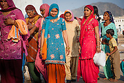 Women in colorful saris by Pushkar lake (India)