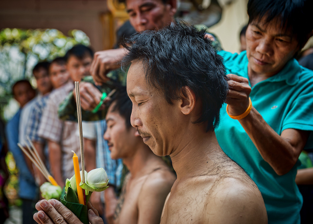 The congregation lines up to take turns clipping a ceremonial lock of hair from the heads of two men who will become Thai Buddhist monks, during a head shaving ceremony in rural ‪‎Thailand‬.
