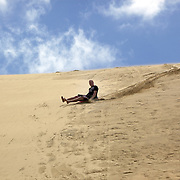 People sliding down the Te Paki Sand dunes on boogie boards. The Te Paki Sand dunes are in the top end of Northland, New Zealand..These giant sand dunes are created by prevailing winds that blow off the Tasman Sea on the West Coast of New Zealand..Te Paki Sanddunes, North Island, Northland, New Zealand. 21st November 2010 Photo Tim Clayton