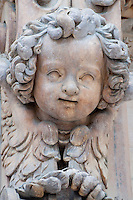 Milan, Italy, Duomo Cathedral - stone angel head sculpture with curly hair.