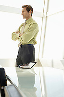Businessman with arms crossed in conference room