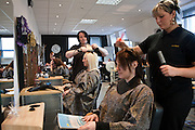 Hairdresser trainees cut the hair of other prisoners during a training session in the prison hair salon. HMP/YOI Askham Grange is a women's open prison serving the Yorkshire area with a capacity of 128 women. It has extensive education, training and mother and Baby facilities.