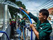 23 AUGUST 2017 - BANGKOK, THAILAND: A Bangkok city worker pours water on the wall of Pom Mahakan before scrubbing it. Bangkok city officials this week started cleaning up the area around cremation site for Bhumibol Adulyadej, the Late King of Thailand. Work started by cleaning Pom Mahakan, a historic fort about two kilometers northeast of the cremation site. They are going to scrub and paint the fort's historic exterior walls, which were built in the late 18th century. The King, who died on 13 October 2016, will be cremated on 26 October 2017.      PHOTO BY JACK KURTZ