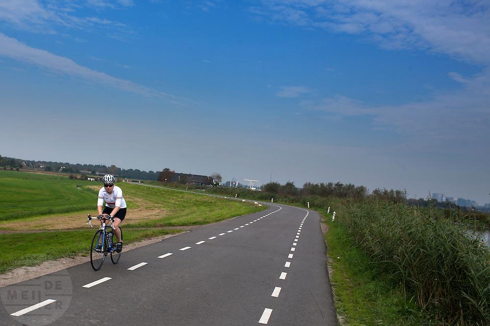 Een wielrenster fietst op haar racefiets langs de Amstel.<br /> <br /> Cyclists are riding nearby the Amstel