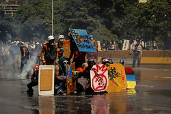 Protesters to the opposition are covered with shields in front of the attacks of tear gas bombs that the Venezuelan National Guard fired to disperse the march destined the Ministry of Interior and Justice in the center of Caracas this May 18, 2017.