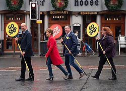 "Edinburgh, Scotland, UK. 18 May 2019. Scotland's First Minister Nicola Sturgeon campaigns alongside lead SNP European candidate Alyn Smith on Leith Walk in Edinburgh. Carrying signs with ""Stop Brexit"" and ""Go SNP"" she used a pedestrian crossing at Pilrig Church"