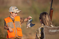 YOUNG BOY WEARING BLAZE ORANGE SHOWING A HARVESTED MOURNING DOVE TO HIS MOTHER