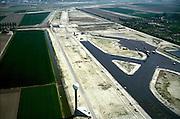 Nederland, Haarlemmermeer, Vijfde baan Schiphol, 17-05-2002; aanleg vijfde baan met rechts 'parkeerplaats' vliegtuigen; naar boven toe (met dubbel viaduct over Hoofdvaart) taxi- of rollerbaan; aan de horizon de Zwanenburgbaan; in de voorgrond (met bol) grondradar; vliegen vliegveld geluidsoverlast infrastructuur, bouwen, planologie ruimtelijke ordening;<br /> luchtfoto (toeslag), aerial photo (additional fee)<br /> foto /photo Siebe Swart