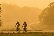 UNITED KINGDOM, London: 18 April 2019 <br /> Cyclists make their way through Richmond Park as the sun rises on what is set to be a warm April's day. Temperatures for the Easter weekend are set to reach 25C.<br /> Rick Findler / Story Picture Agency