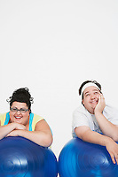 Happy overweight man and woman Resting on Exercise Balls front view