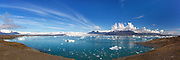 Jökulsárlón is a large glacial lagoon in southeast Iceland, on the borders of Vatnajökull National Park. Situated at the head of Breiðamerkurjökull, it evolved into a lagoon after the glacier started receding from the edge of the Atlantic Ocean. You can see Vestra-Miðfell in the background. This picture is a stitched panorama | Jøkulsarlon er en stor isbrelagune på sørøst island, på grensen til Vatnajøkull Nasjonalpark. Der den ligger på enden av Breidamerkurjøkull har den gradvis truk ket seg tilbake fra kanten av Atlanterhavet og dannet en fantastisk fin isbrelagune. Dette bildet er et panorama, sett sammen av flere enkelteksponeringer.