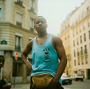 Teenage boy in Paris wearing a bum bag and blue vest