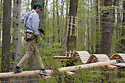 Steve Fuller, Project Manager at Bristol Mountain's new Aerial Adventure Park, crosses an obstacle on Tuesday, May 20, 2014.