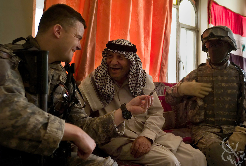 """)U.S. Army 2-325, 82nd Airborne Division Lt. Paul Benfield (l), from Old Town, Florida jokes with Iraqi Sheikh Aedan Ash al-Kabi during a patrol in the Shaab district of Baghdad, Iraq June 03, 2007. Across Baghdad, the """"Surge"""" of U.S. forces enters it's fifth month with mixed results....."""