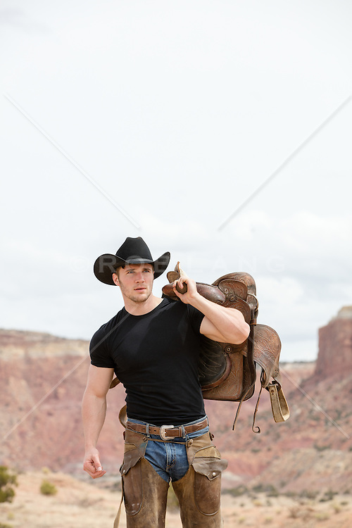 cowboy walking with a saddle on a mountain range