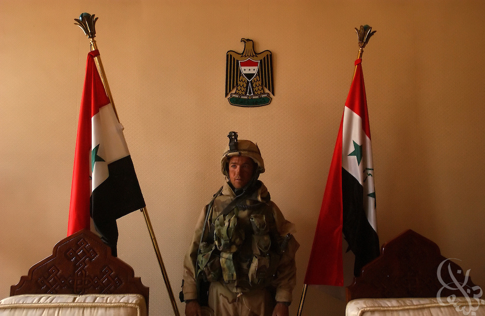 U.S. Army 3rd Division 3-7 Platoon Leader Lieutenant Mike Washburn from Yorktown, Virginia, jokingly poses in front of Iraqi flags after leading his platoon April 4, 2003 on a sweep of the VIP terminal of Baghdad International Airport during a dawn advance on the Iraqi capital.